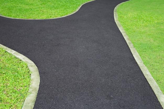 El camino en el parque con la hierba verde. Foto Premium