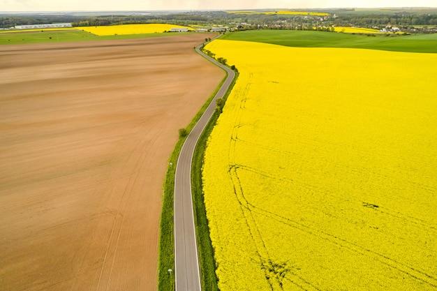 Un camino rural separaba los campos de colza vacíos y amarillos con un patrón dejado por la cosechadora. vista superior del campo agrícola en primavera. Foto Premium