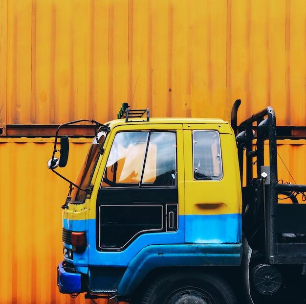 Camión amarillo estacionado cerca de una caja de contenedor amarillo Foto gratis