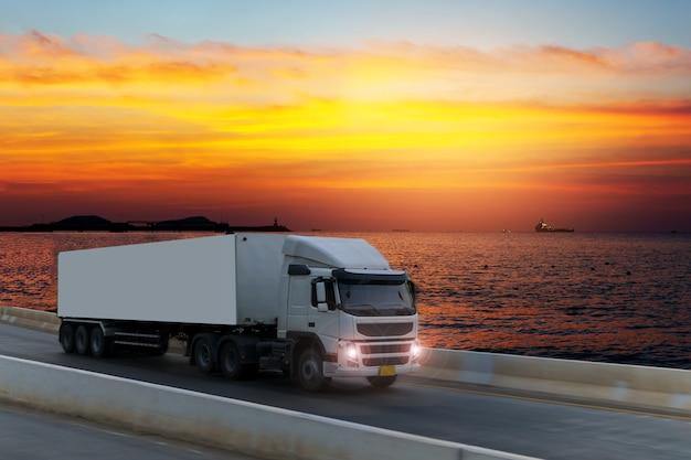 Camión blanco en carretera con contenedor, importación, exportación logística industrial transporte. Foto Premium