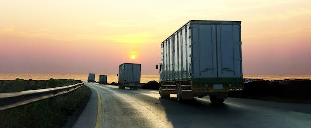 Camión en carretera con contenedor, transporte industrial logístico con cielo de amanecer Foto Premium