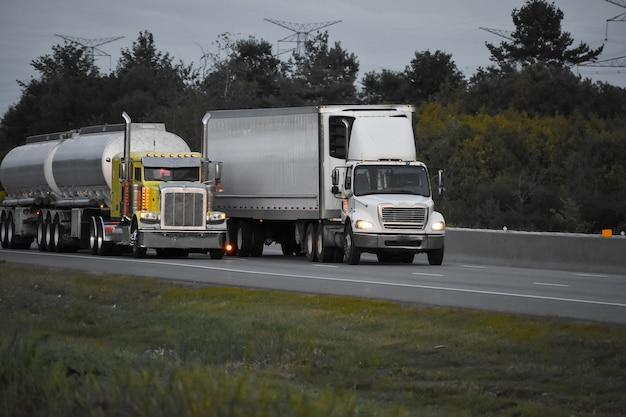 Camiones de remolque circulando por la carretera rodeada de hermosos árboles verdes Foto gratis
