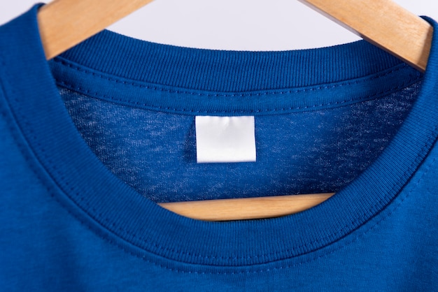 Camiseta azul en blanco y etiqueta en blanco para publicidad. Foto gratis