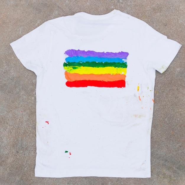 Camiseta con el emblema del arcoiris sobre asfalto. Foto gratis