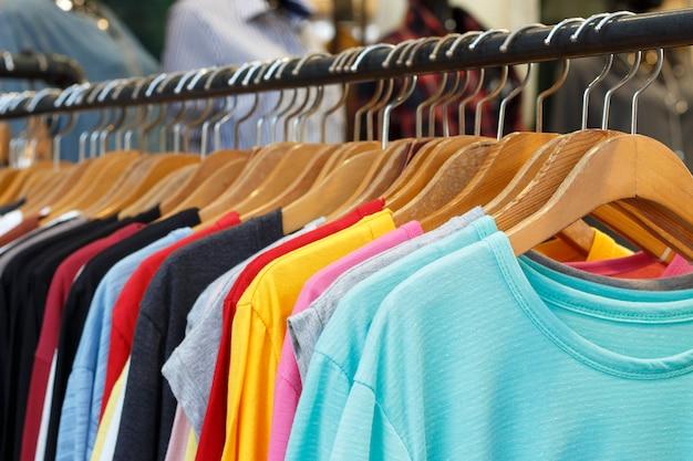 Camisetas multicolores con mangas largas en perchas de madera, vista lateral. Foto Premium