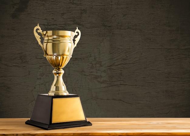 Campeón de oro trofeo en mesa de madera con espacio de copia Foto Premium