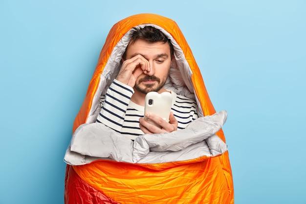 El campista masculino cansado se frota los ojos, usa el teléfono móvil, intenta conectarse a internet en la naturaleza salvaje, posa en un saco de dormir, tiene todo el equipo necesario para acampar Foto gratis