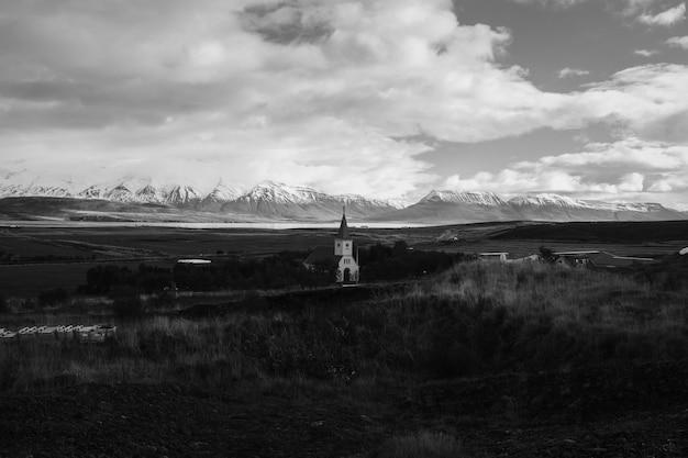 Un campo con una iglesia en la distancia con hermoso cielo nublado Foto gratis