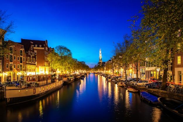 Canales de amsterdam en la noche en holanda. amsterdam es la capital y la ciudad más poblada de los países bajos. Foto Premium