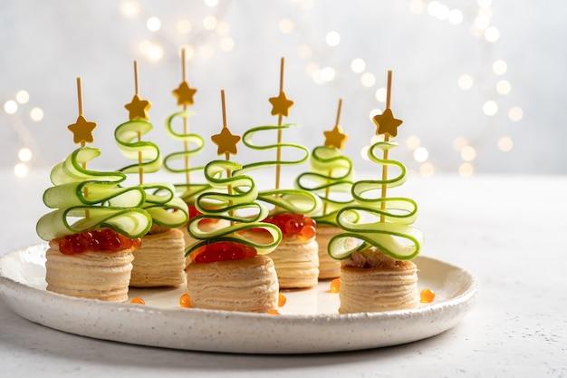 Canapé de árbol de navidad con rodaja de pepino, paté de salmón y caviar rojo para la merienda navideña Foto Premium