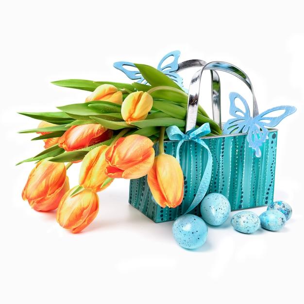 Canasta de pascua con tulipanes, huevos y mariposas de madera en blanco Foto Premium