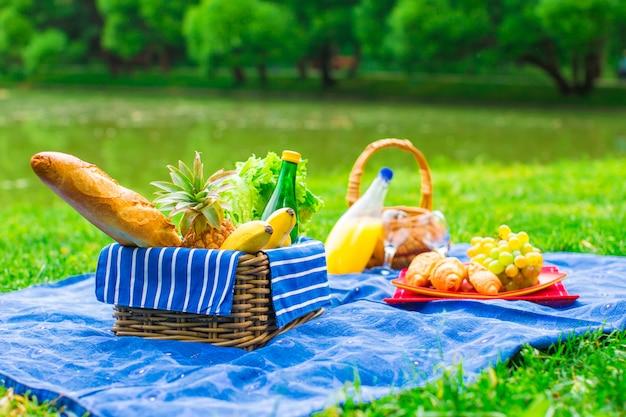Canasta de picnic con frutas, pan y botella de vino blanco. Foto Premium