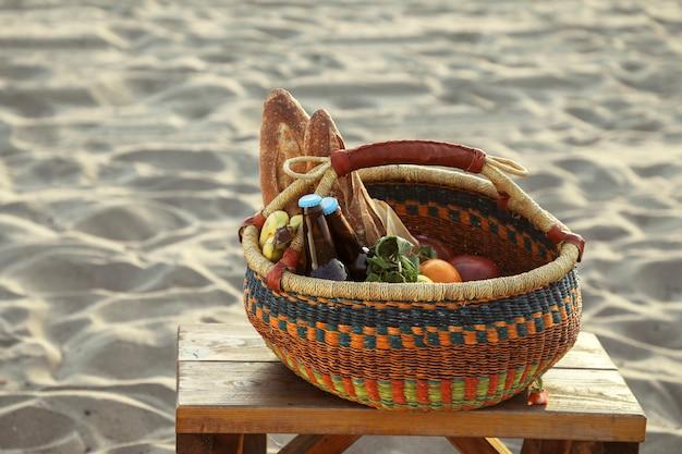 Canasta de picnic llena de bocadillos y bebidas en la playa. Foto gratis