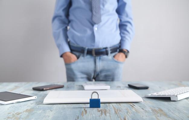 Candado en el escritorio. hombre de pie en la oficina. seguridad de internet y tecnología Foto Premium