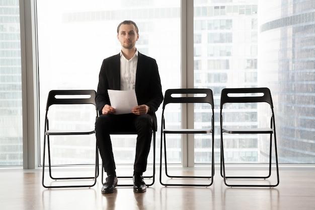 Candidato en el puesto sentado en silla con curriculum vitae Foto gratis
