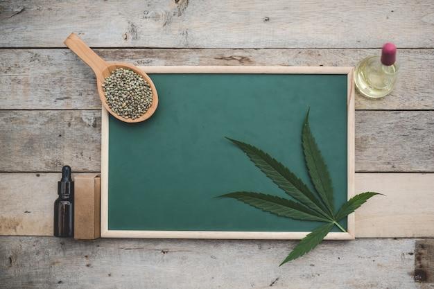 Cannabis, semillas de cannabis, hojas de cannabis, colocadas en el tablero verde y hay aceite de cáñamo al lado en el piso de madera. Foto gratis