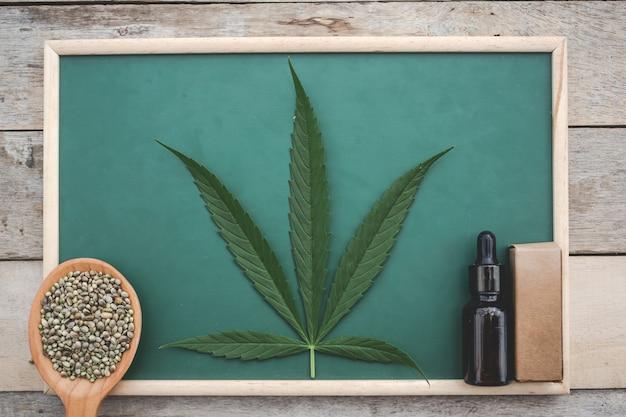 Cannabis, semillas de marihuana, hojas de marihuana, aceite de marihuana colocado en un tablero verde sobre un piso de madera. Foto gratis