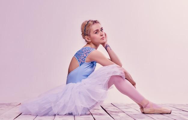 Cansado bailarín sentado en el piso de madera Foto gratis