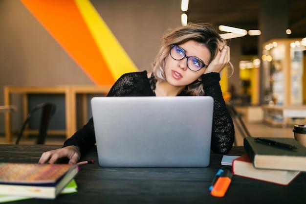Cansado triste joven mujer bonita sentada en la mesa trabajando en la computadora portátil en la oficina de trabajo conjunto, con gafas, estrés en el trabajo, emoción divertida, estudiante en la sala de clase, frustración Foto gratis