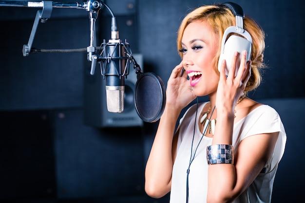 Cantante asiática produciendo canción en estudio de grabación. Foto Premium