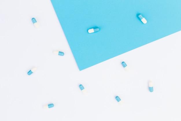 Cápsulas sobre fondo azul y blanco Foto gratis
