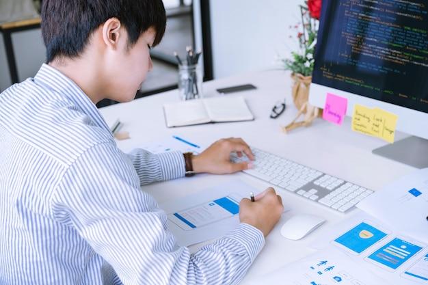 Captura recortada del diseñador de aplicaciones móviles que diseña el diseño de pantallas de estructura alámbrica móvil para codificar o programar aplicaciones móviles. Foto Premium