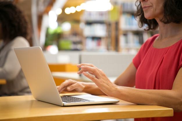 Captura recortada de mujer caucásica trabajando con la computadora portátil en la biblioteca Foto gratis