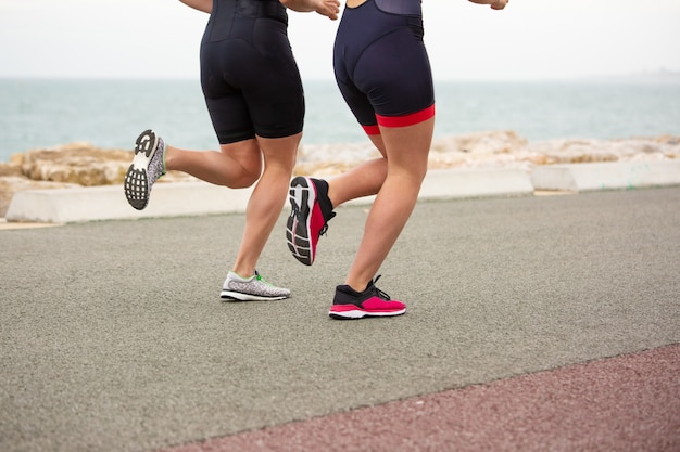 Captura recortada de mujeres corriendo en la orilla del mar Foto gratis