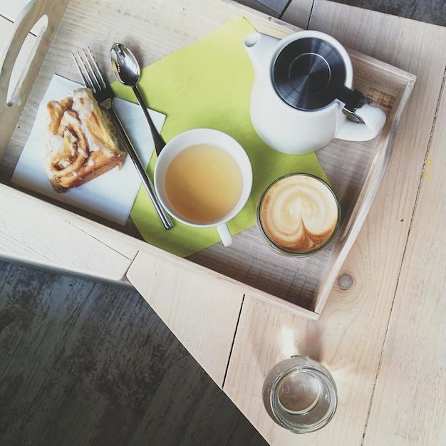 Capuchino de café y té con bollo de canela en una cafetería Foto gratis