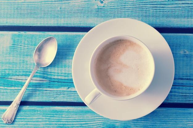Capuchino en una taza blanca sobre mesa azul Foto Premium