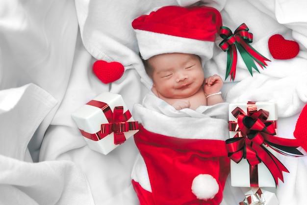 Cara De Bebé Recién Nacido Durmiendo En Gorro Navideño Con Caja De