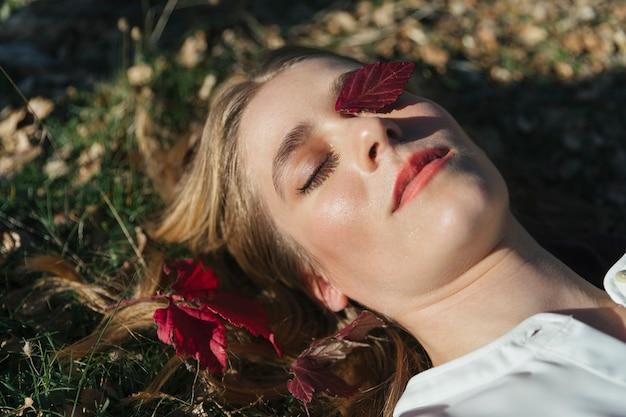 Cara brillante de mujer con hoja en ojo Foto gratis