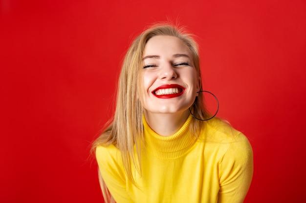 La cara de la muchacha de la diversión del primer que ríe mirando a la cámara - sonrisa amplia Foto Premium