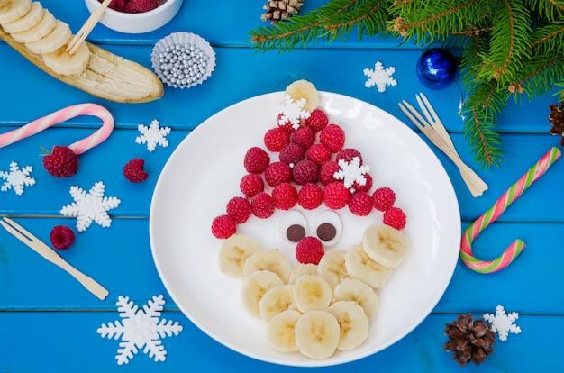 Cara de papá noel hecha de frambuesas y plátano con chocolate. idea  divertida de comida para navidad y año nuevo   Foto Premium