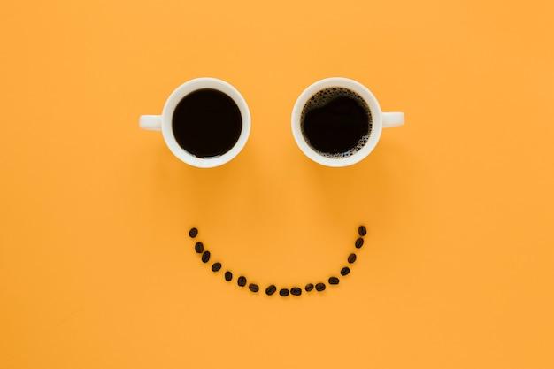 Cara sonriente de tazas de café y frijoles Foto gratis