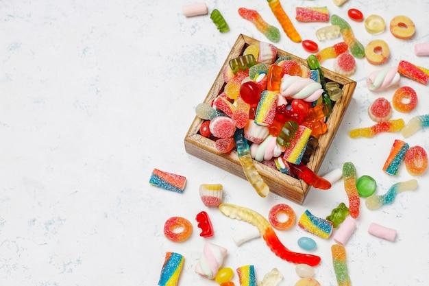 Caramelos de colores, gelatina, malvavisco en la superficie de la luz. vista superior con espacio de copia Foto gratis