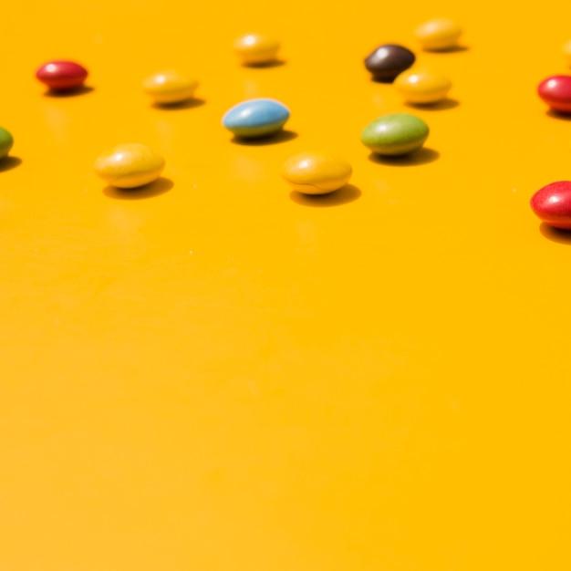 Caramelos con espacio de copia para escribir el texto sobre fondo amarillo Foto gratis