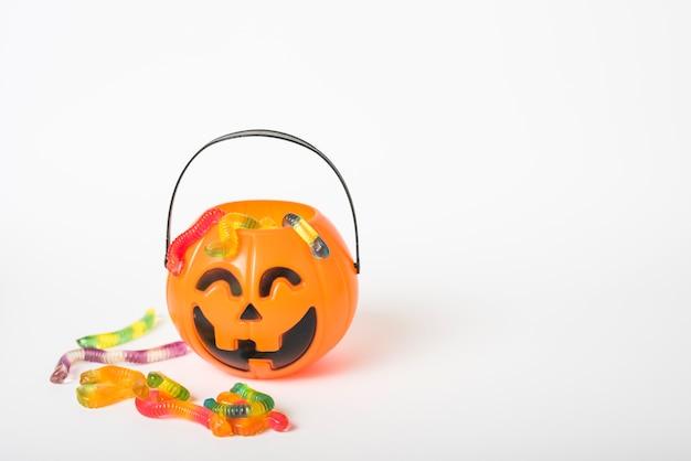 Caramelos de gelatina cerca de la cesta de jack-o-lantern Foto gratis