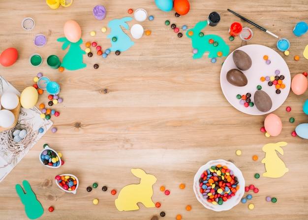 Caramelos de gemas de colores; huevos de pascua; colores y pincel en escritorio de madera Foto gratis
