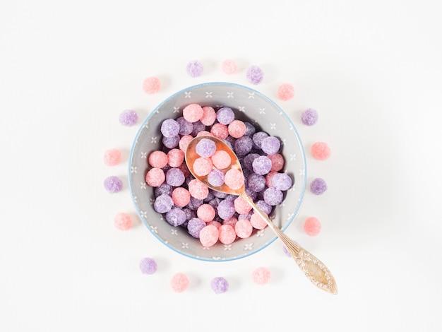 Caramelos morados y rosados en un tazón Foto Premium