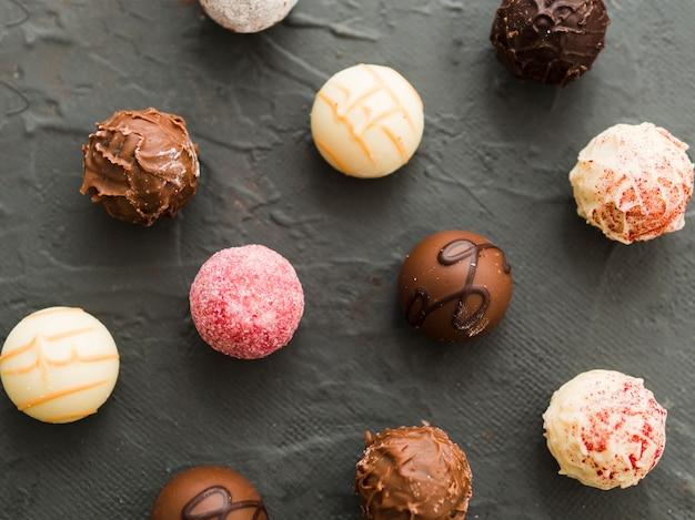 Caramelos redondos de chocolate sobre fondo negro desde arriba Foto gratis