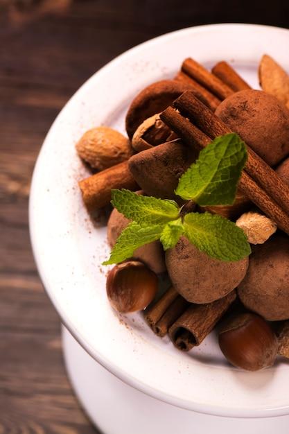 Caramelos de trufas de chocolate y surtido de nueces en soporte blanco Foto Premium