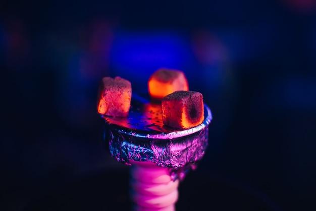 Carbones rojos calientes de tabaco en el tazón de shisha en la lámina de cerca Foto Premium
