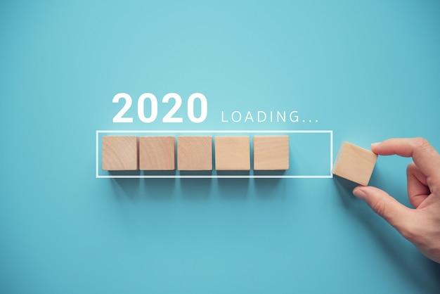Cargando el nuevo año 2020 con la mano poniendo el cubo de madera en la barra de progreso. Foto Premium