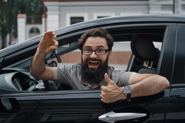 Carismático hombre sosteniendo las llaves del auto mostrando los pulgares para arriba Foto gratis