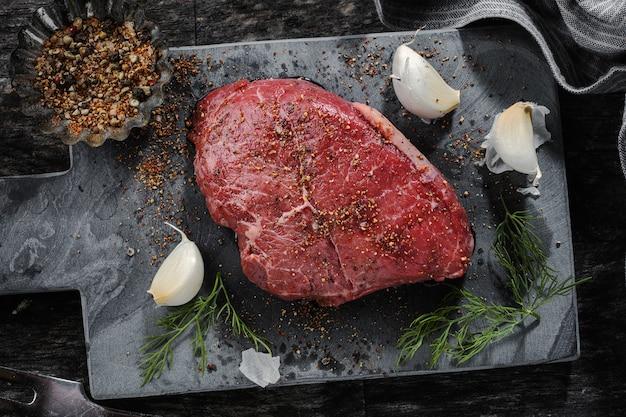 Carne cruda con especias en superficie oscura. listo para cocinar. Foto gratis