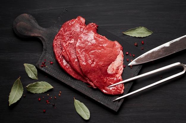 Carne cruda fresca sobre tabla de madera con cuchillo y hierbas Foto gratis