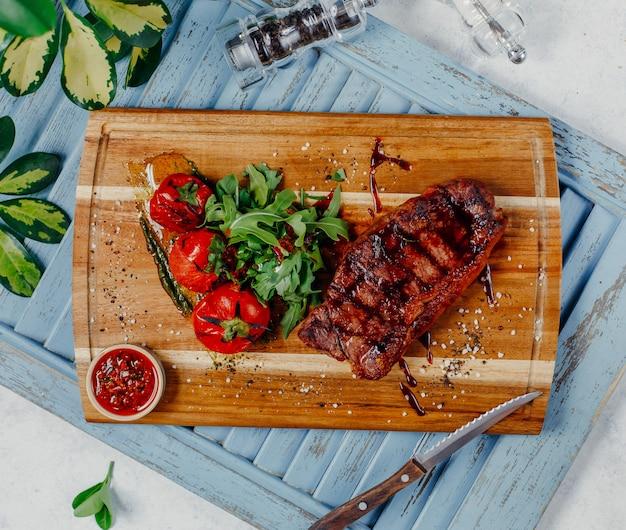 Carne frita con verduras en la vista superior del tablero de madera Foto gratis