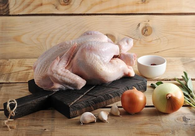 Carne de pollo cruda entera en el tablero y especias Foto Premium