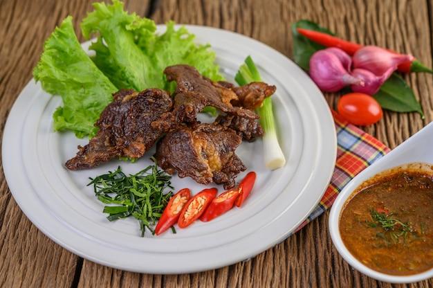 Carne de res frita comida tailandesa en un plato blanco con cebolleta, hojas de lima kaffir, chiles, ensalada, cebolla roja y tomates. Foto gratis